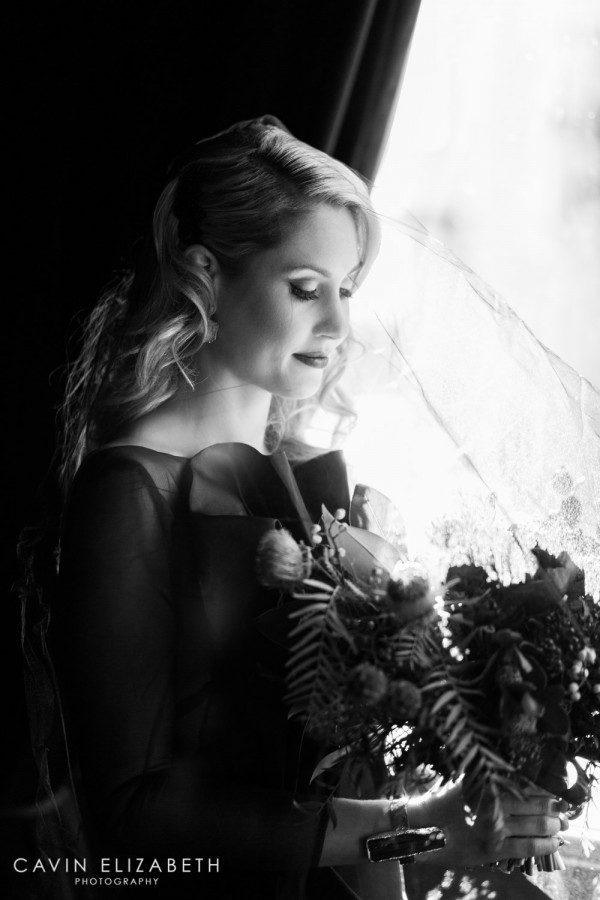 Moody bride in black with veil and bouquet